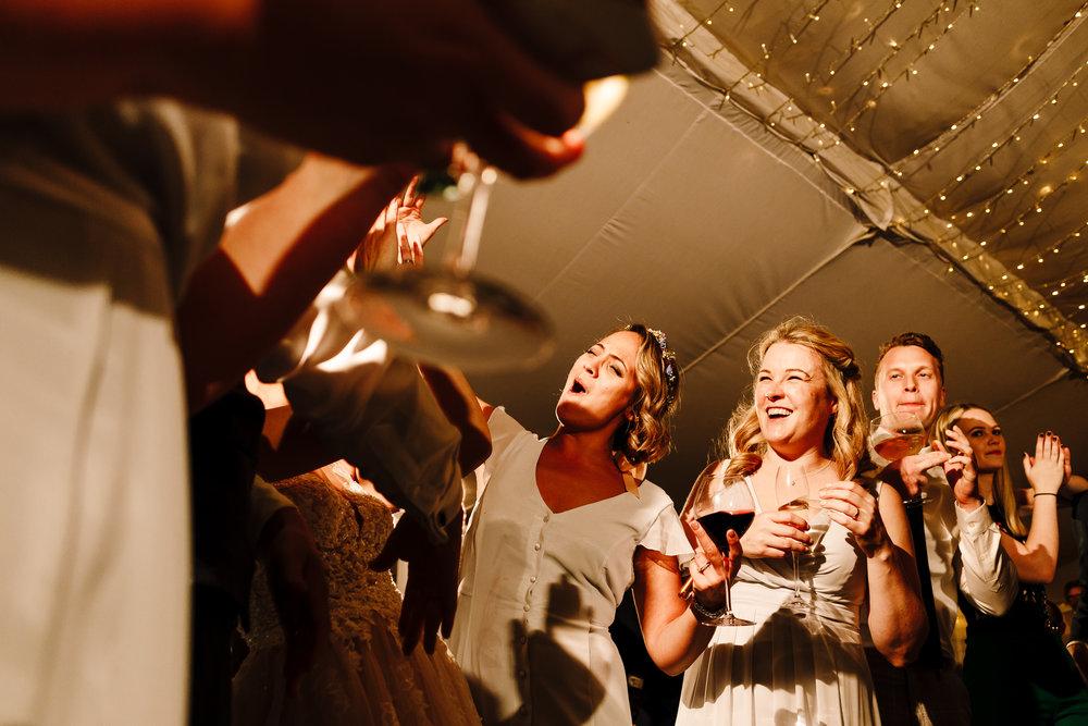 Bridesmaids and guests drinking and dancing at a reception