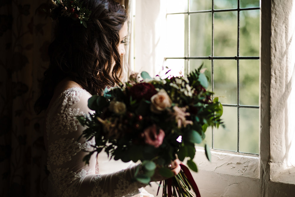 A bride holding her bouquet looking out the window before the wedding