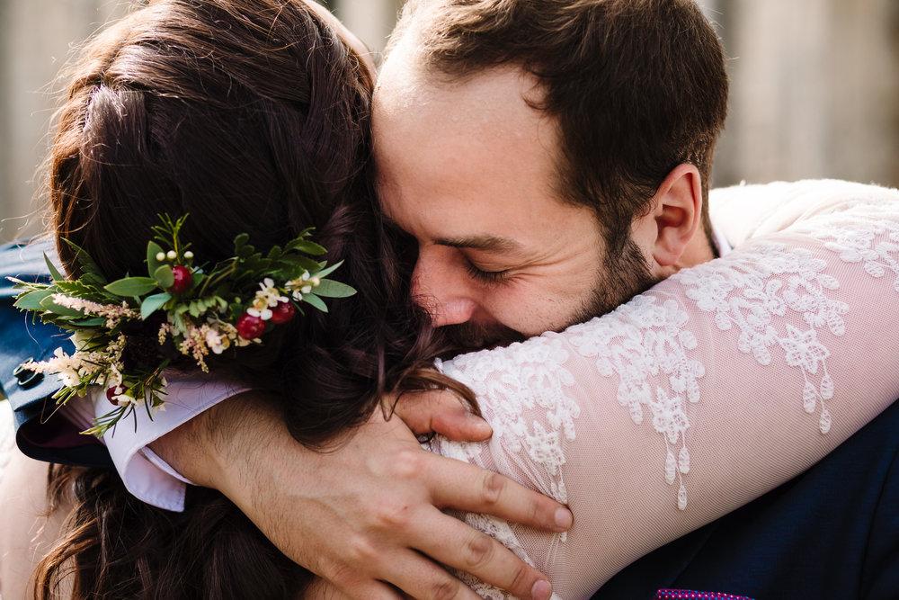 A close up shot of a wedding guest hugging the bride