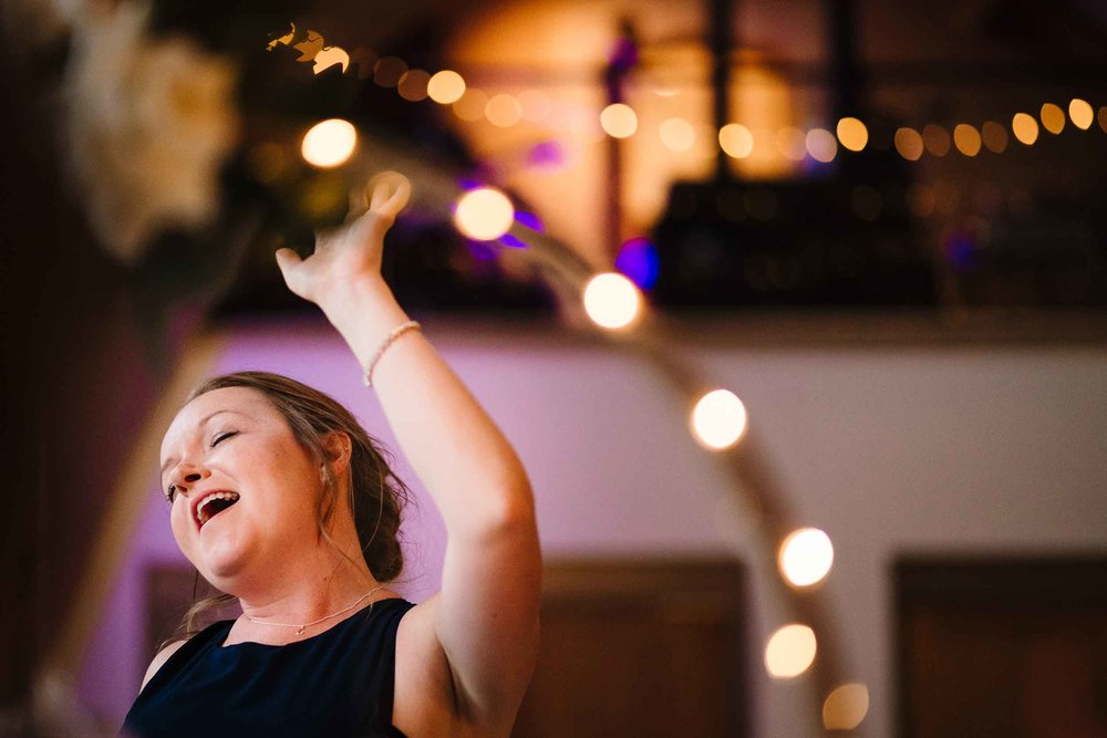 a bridesmaid at a wedding singing with her eyes closed