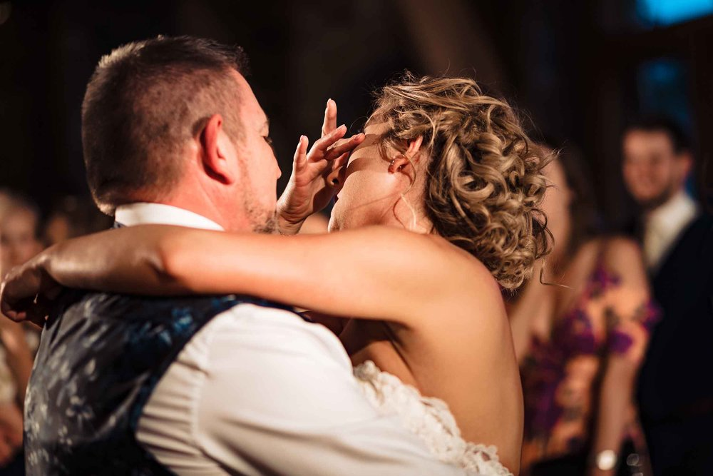 a bride crying as she dances with her father at her wedding
