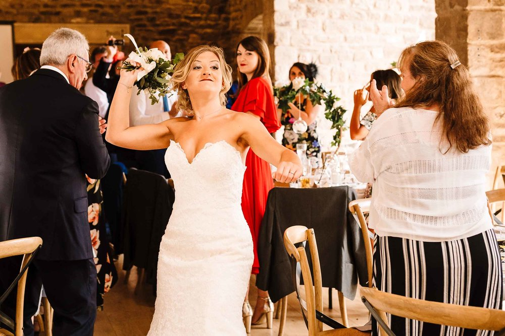 a bride being silly about to throw her bouquet