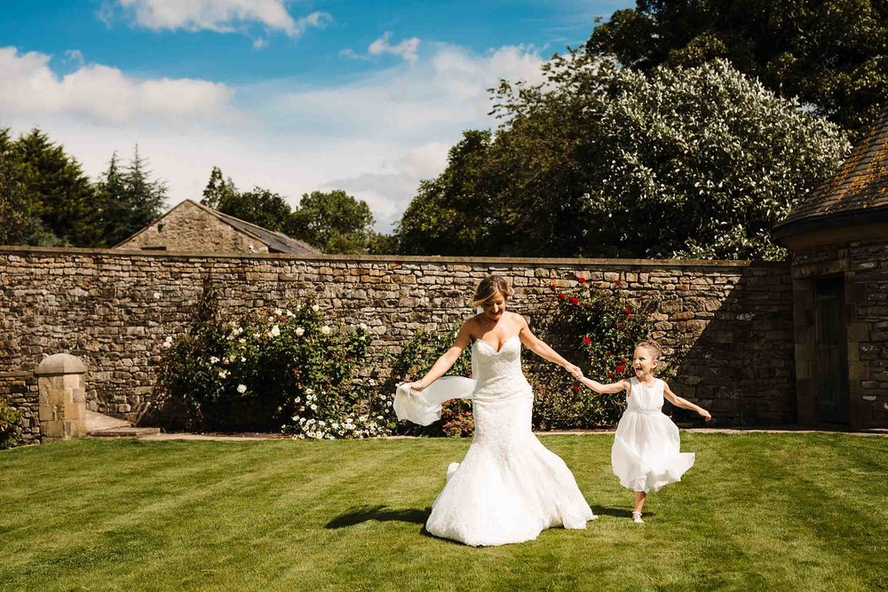a bride running with her step daughter at a wedding in yorkshire