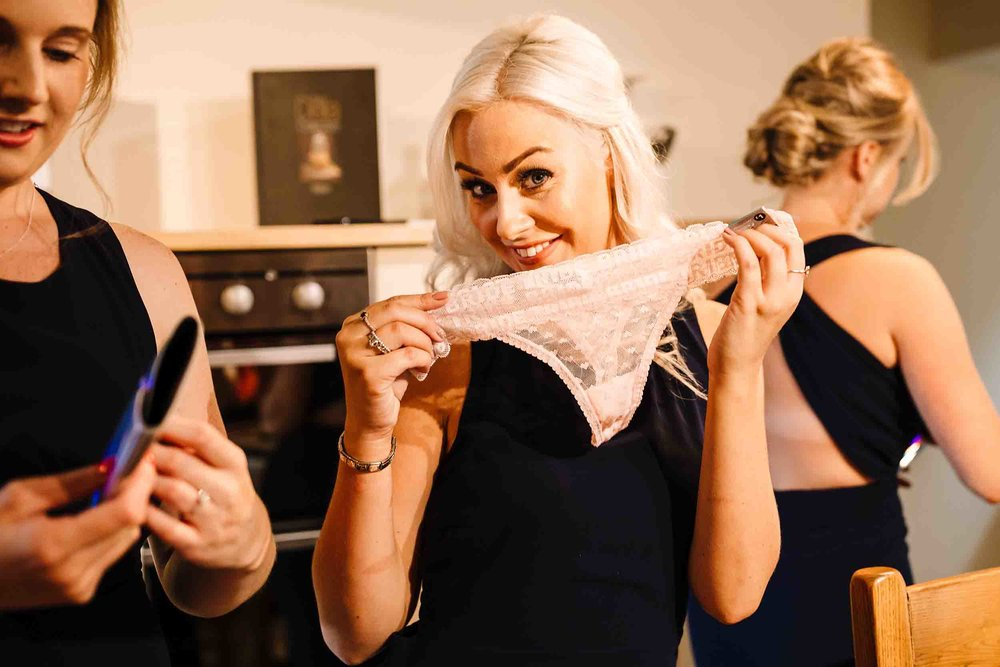 a bridesmaid holding a lacey thong