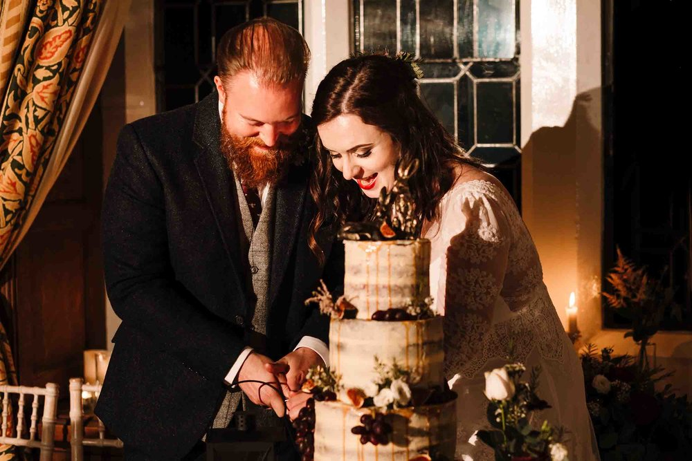 a bride and groom cutting their cake