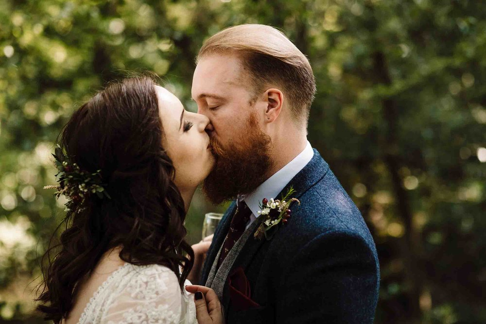 a bride and groom kissing in a forest