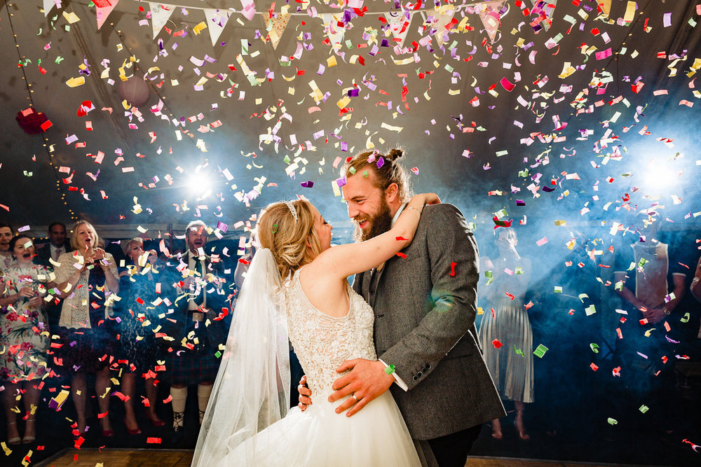 A bride and groom dancing surrounded by colourful confetti