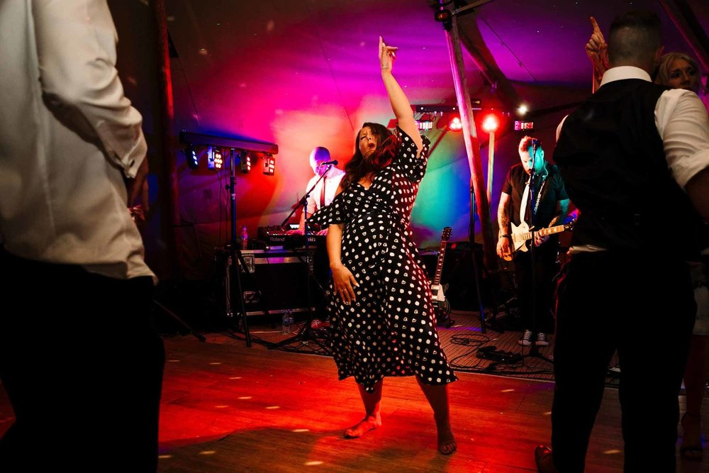 A wedding guest with no shoes on pointing into the sky and singing on the dance floor in a tipi in Yorkshire