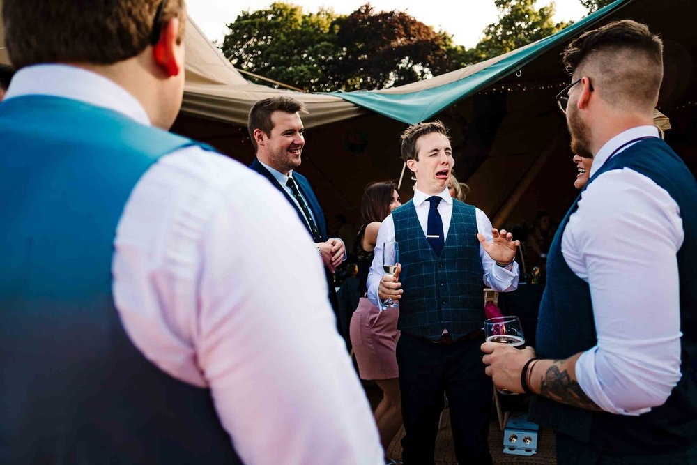 A groom pulling a funny face after drinking a shot