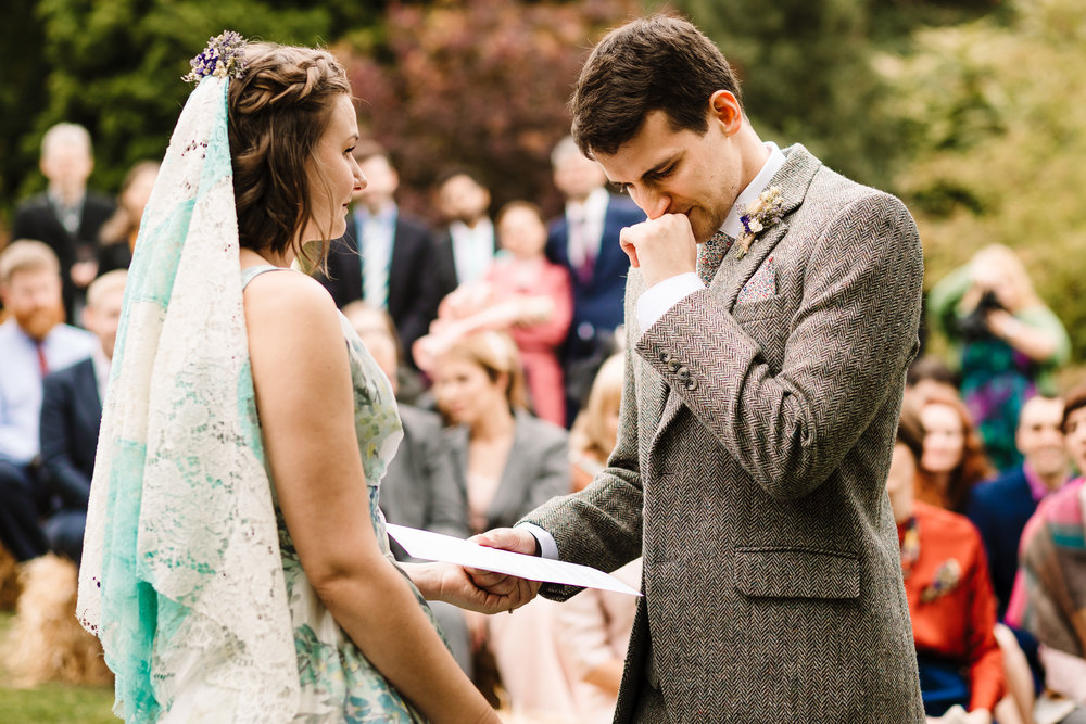 A groom crying as he tries to say his vows in an outdoor garden ceremony