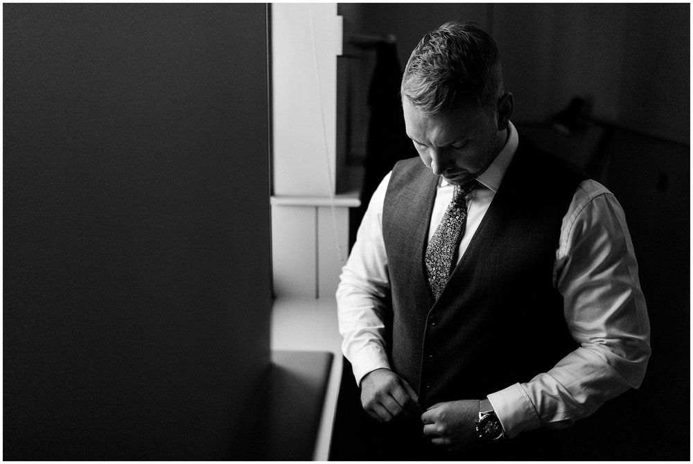 A black and white image of a groom doing up his waistcoat