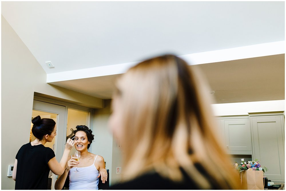 A bride laughing and drinking champagne as she has her makeup done