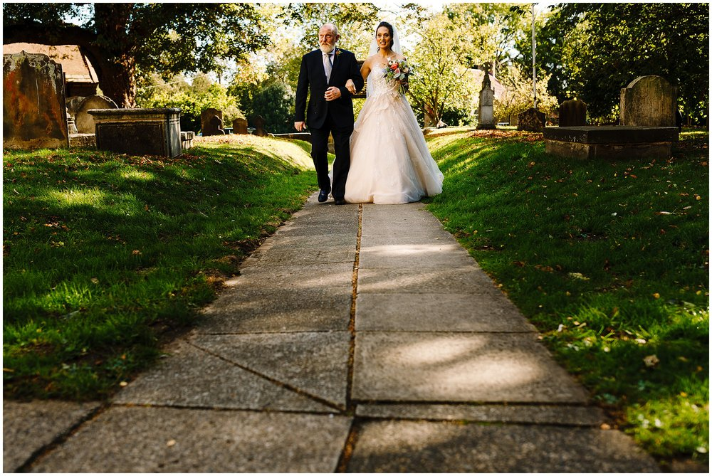 A bride walking towards the church arm in arm with her dad
