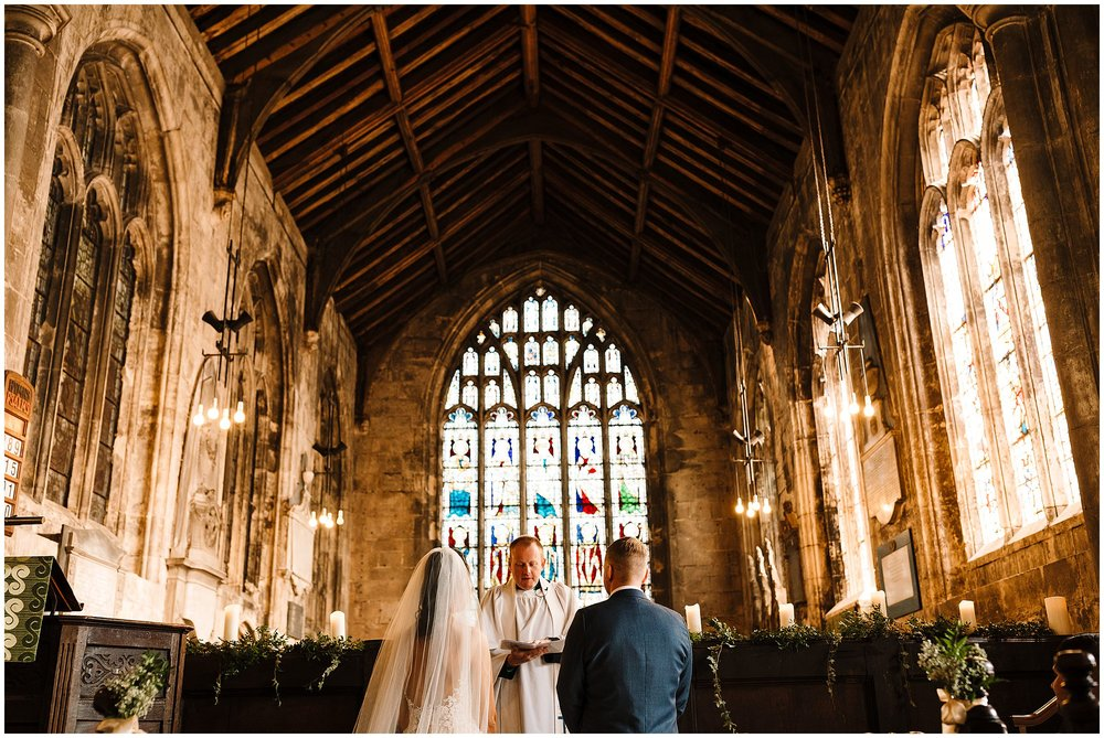 A wide shot of the bride and groom kneeling at the alter in All Saints Church Bolton Percy