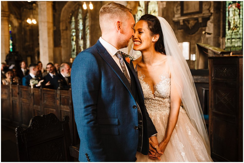 A bride and groom laughing and touching noses after saying I do