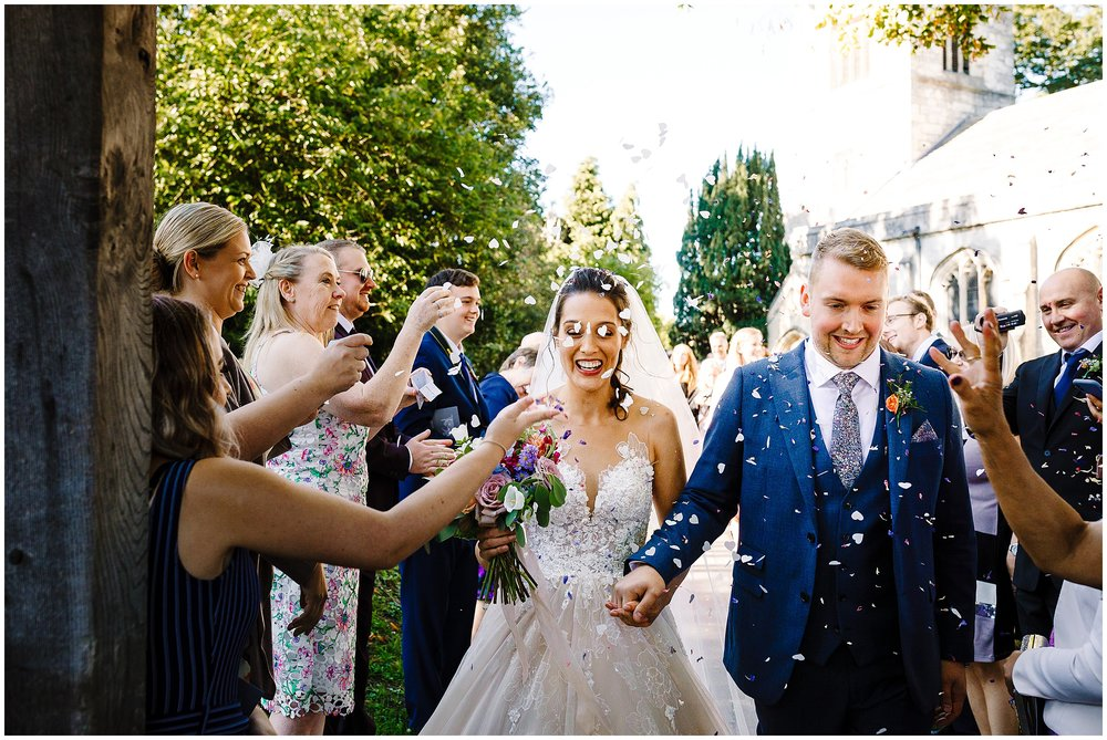 A bride and groom walking out of the church yard as guests throw confetti at them