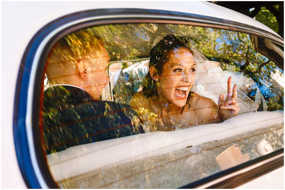 A bride being silly sticking two fingers up at her friends through the back window of the wedding car