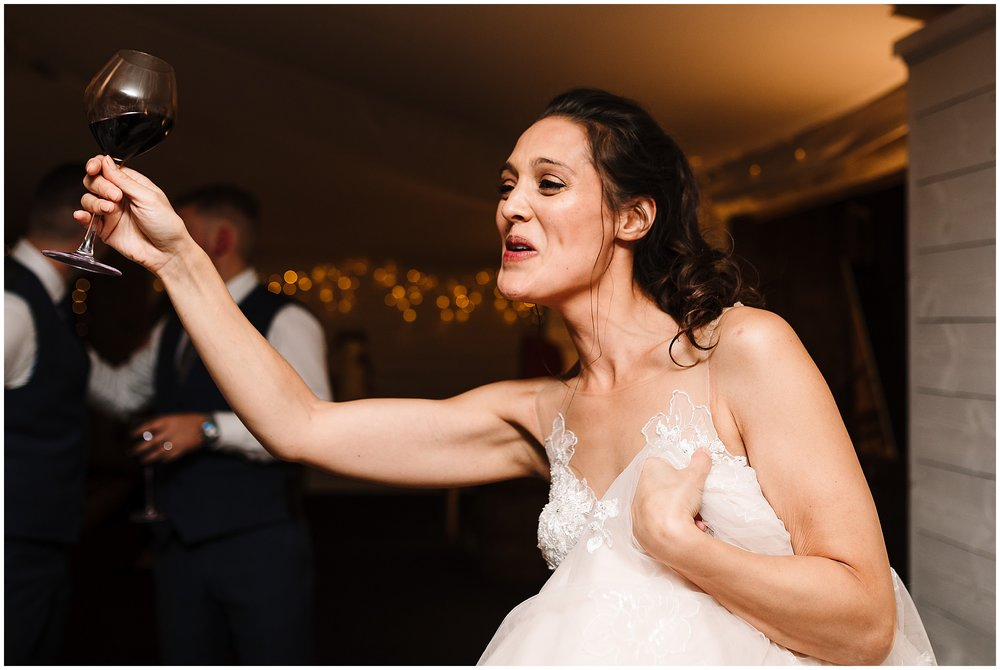 A bride holding a glass of red wine in the air