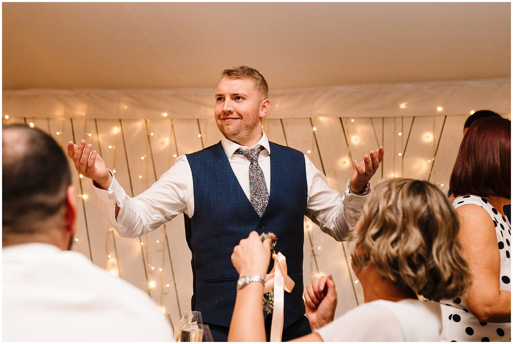 A groom pulling a funny face during his speech