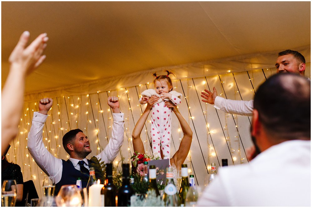 A bride holding her baby in the air as everyone cheers
