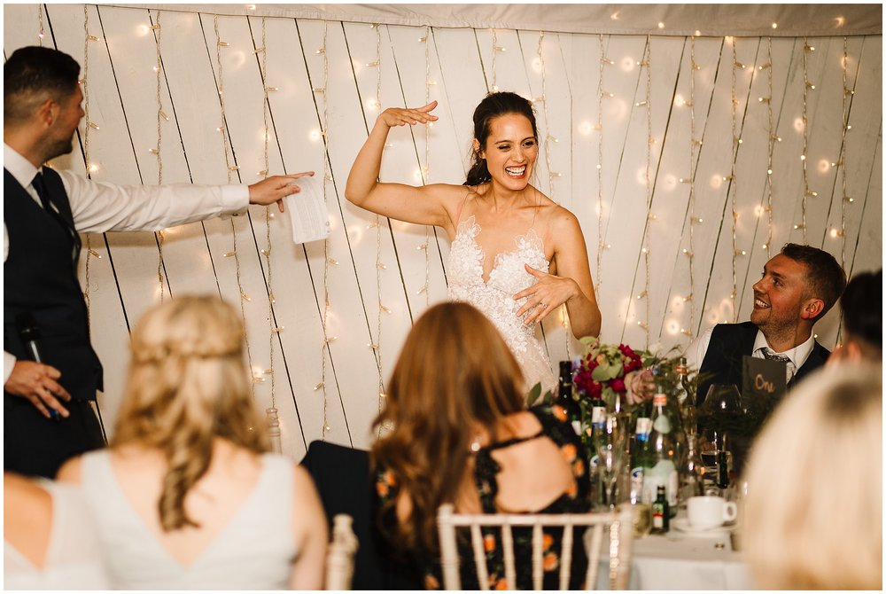 A bride bring silly during speeches as the best man points at her