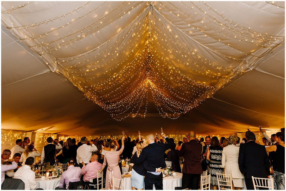 A wide shot of the reception room as everyone holds their glasses in the air