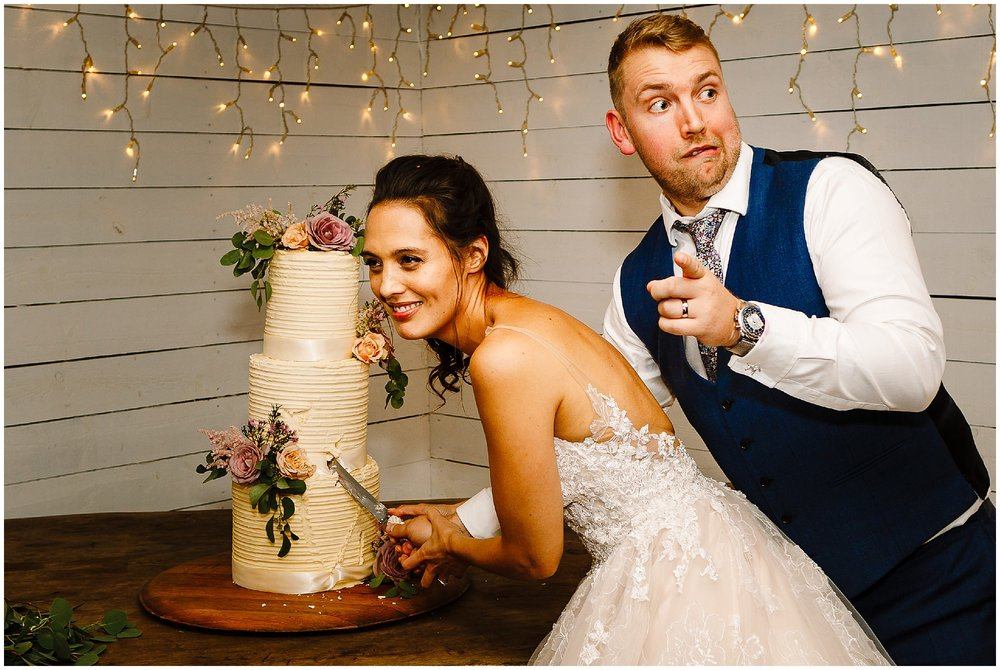 A very drunk bride and groom trying to cut the cake and pulling funny faces