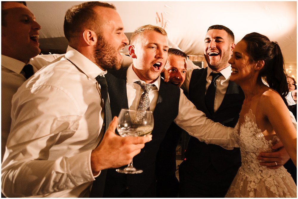 The bride and groom singing and dancing with their friends