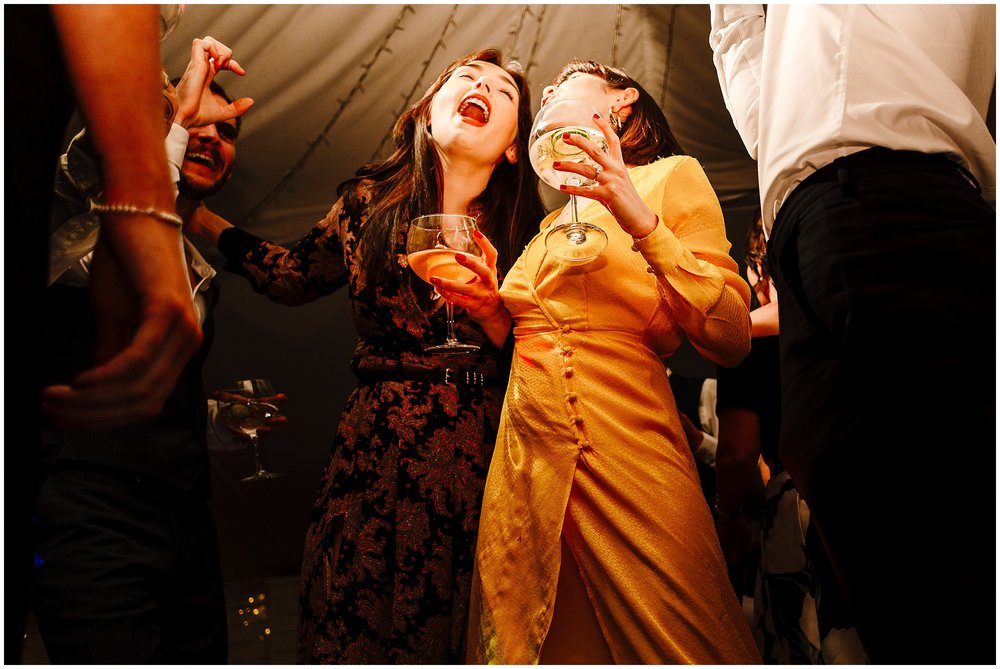 Two wedding guests singing and drinking gin on the dance floor