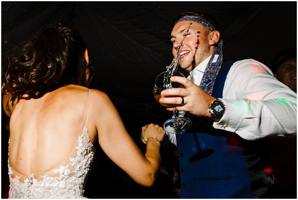 A groom dancing as his drink is suspended in mid air about to spill
