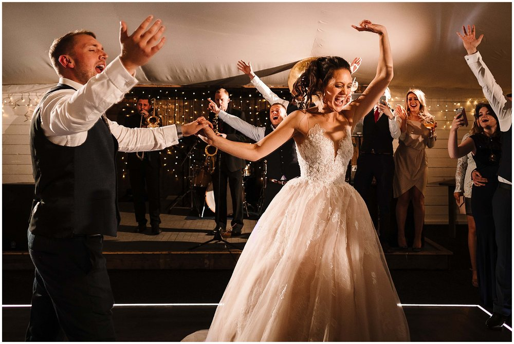 A bride and groom jumping around during their first dance as the New York Brass Band plays behind them