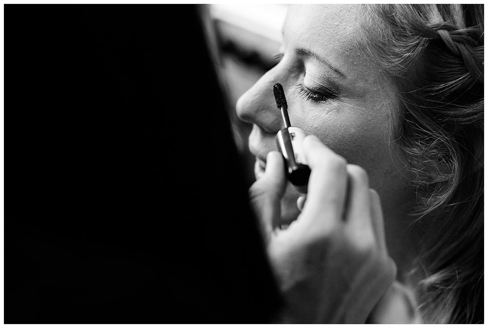 A black and white image of a bridesmaid having her mascara applied by a makeup artist
