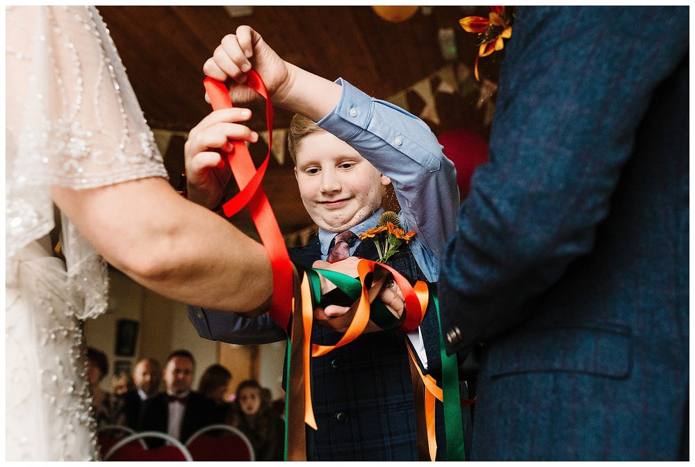 A young boy tying colourful ribbon around a bride and groom's hands during a hand fasting ceremony