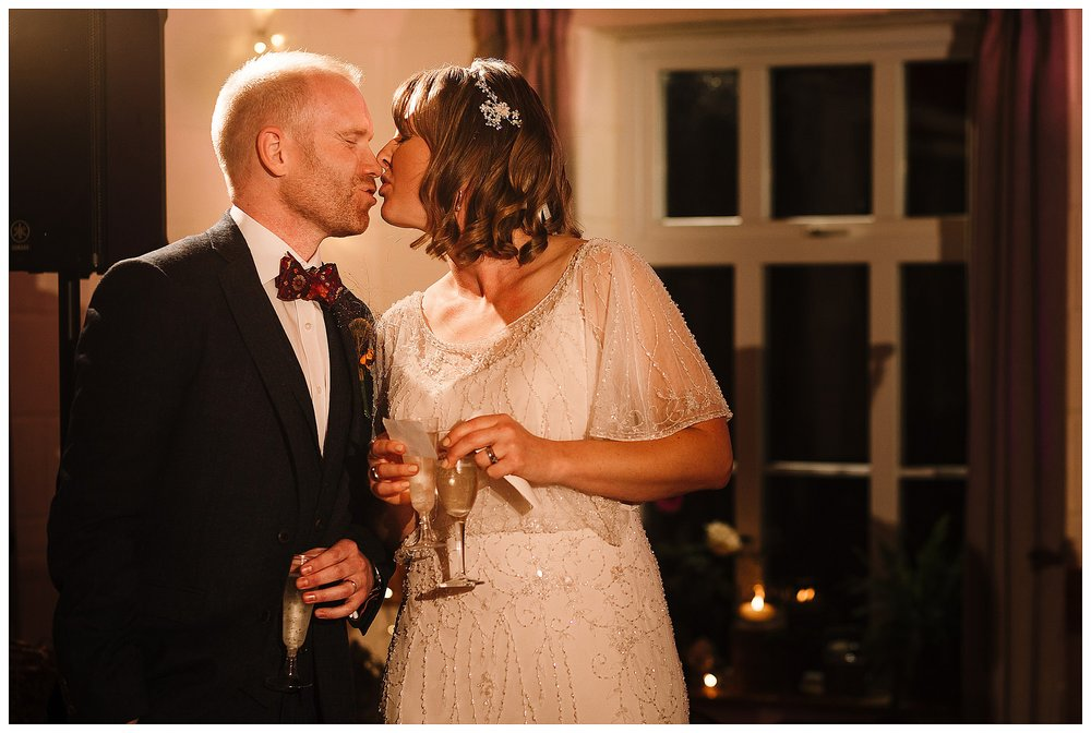 A bride and groom kissing during speeches
