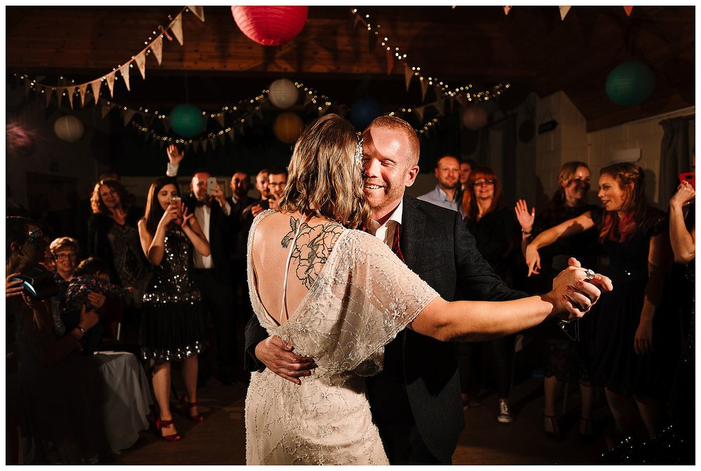 A bride and groom doing their first dance with guests gathered behind them
