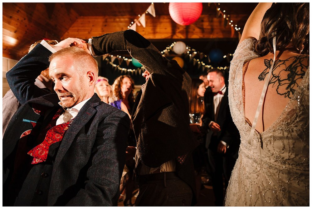 A groom pulling a funny face as he dances