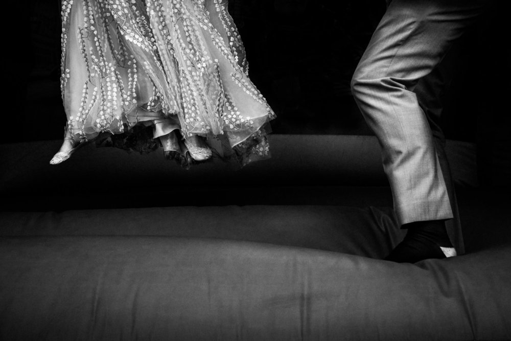 A black and white image of a bride and groom's feet on a bouncy castle