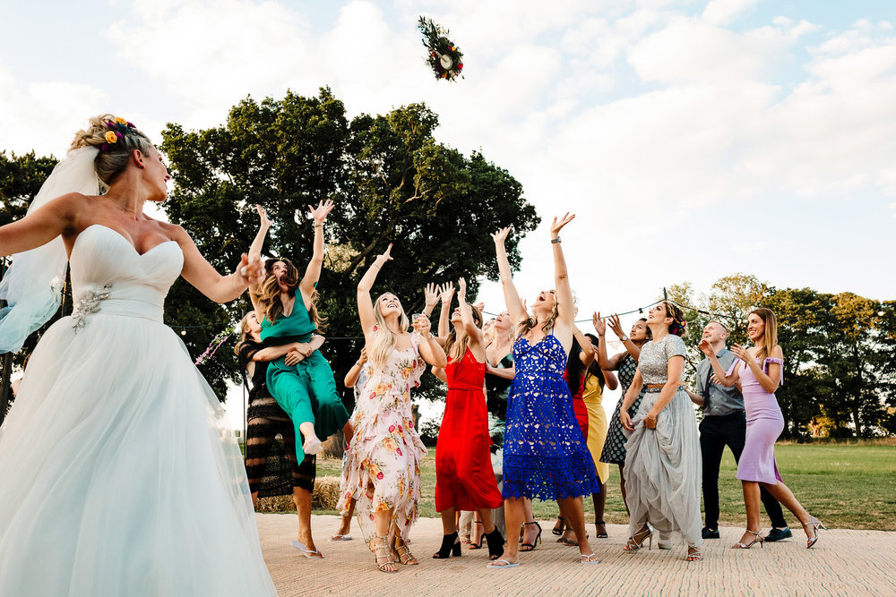 A bride tossing her bouquet into a crowd of female guests
