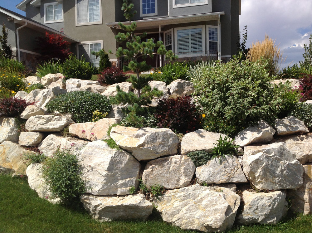 Rock Retaining Walls - A natural rock retaining wall provides structural support for sloped landscapes. Rock retaining walls can also be used to maximize your usuable space without compromising style.