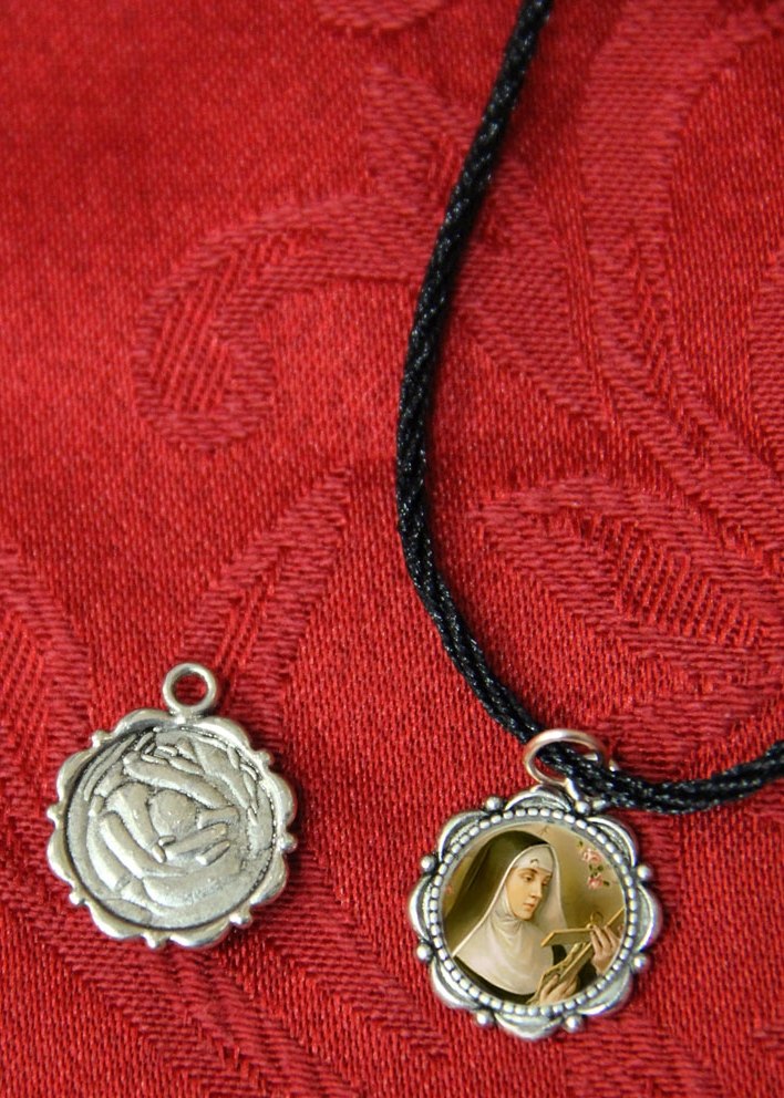 - $3                                                                    Handmade Saint Rita flower alloy pendant with diameter of 14mm, comes with an 8 inches Black Cord.