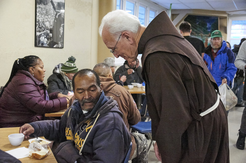 Fr. Michael Duffy, OFM with a guest at St. Francis Inn Ministries Food Kitchen.