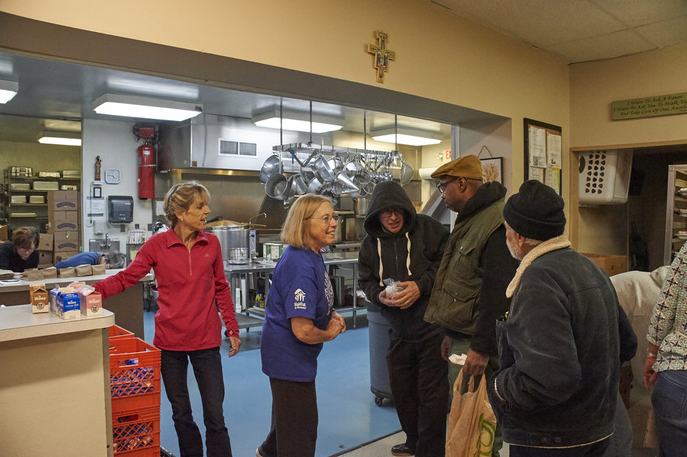 Volunteers talk with guests receiving toiletries at St. Francis Inn Ministries.
