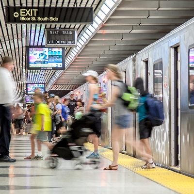 A picture of a people exiting a train in a busy subway station in Toronto.