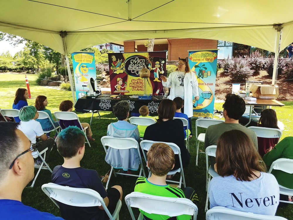 A group watching a presentation of Mad Scientist under the community tent at our 2017 EcoFest festival.