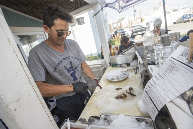 Ian Wile shucking at Little Creek Oysters in Greenport on a Saturday afternoon in July. (Credit: Randee Daddona)