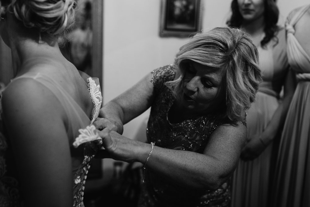 Downtown Denver wedding at Moss. Colorado wedding photographer. Mom helping put on dress.