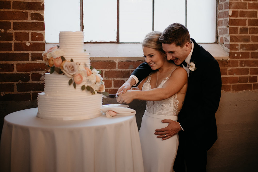 Bride and groom cut cake. Wedding at Moss in Denver. Downtown Denver wedding photographer.