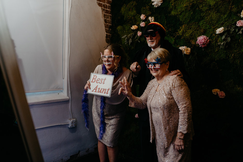 Guests using photobooth at wedding at Moss in Denver. Colorado wedding photographer.