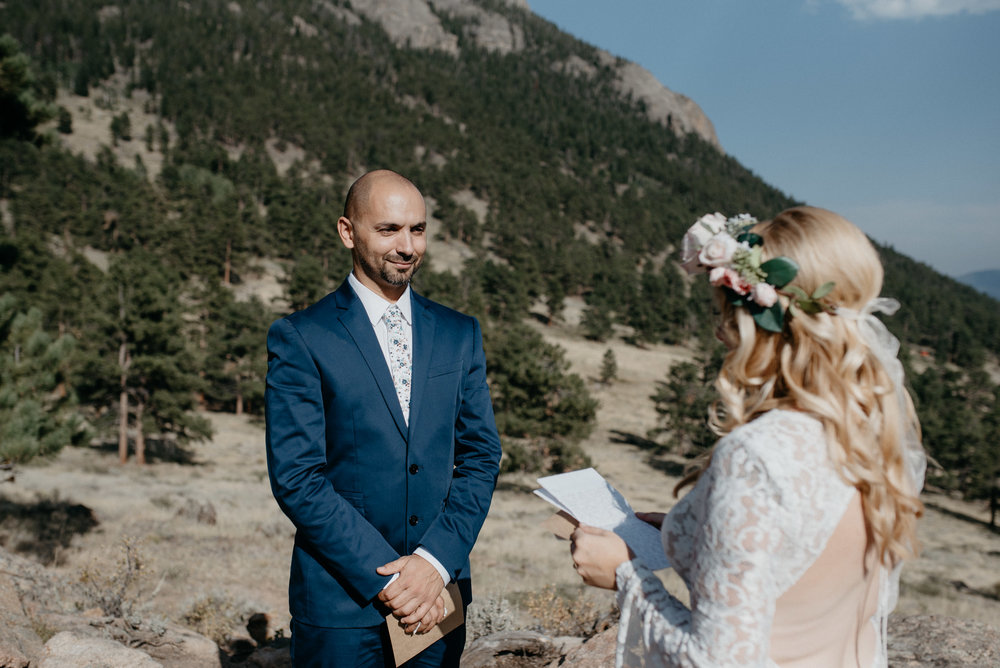 Ceremony at 3M curve in Colorado. Bride and groom exchanging vows.