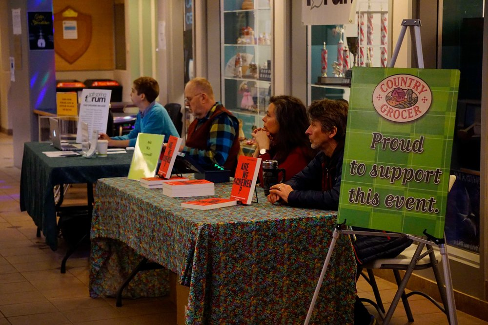 Forum youth volunteer Sef Everest and Forum board member Jim Erickson work at the Forum information booth (far left). Adina Hildebrandt and Andrew Haigh (right) of Salt Spring Books sell Geoff Dembicki's new book  Are We Screwed: How a New Generation is Fighting to Survive Climate Change.    *Photo take by Philipp Klein